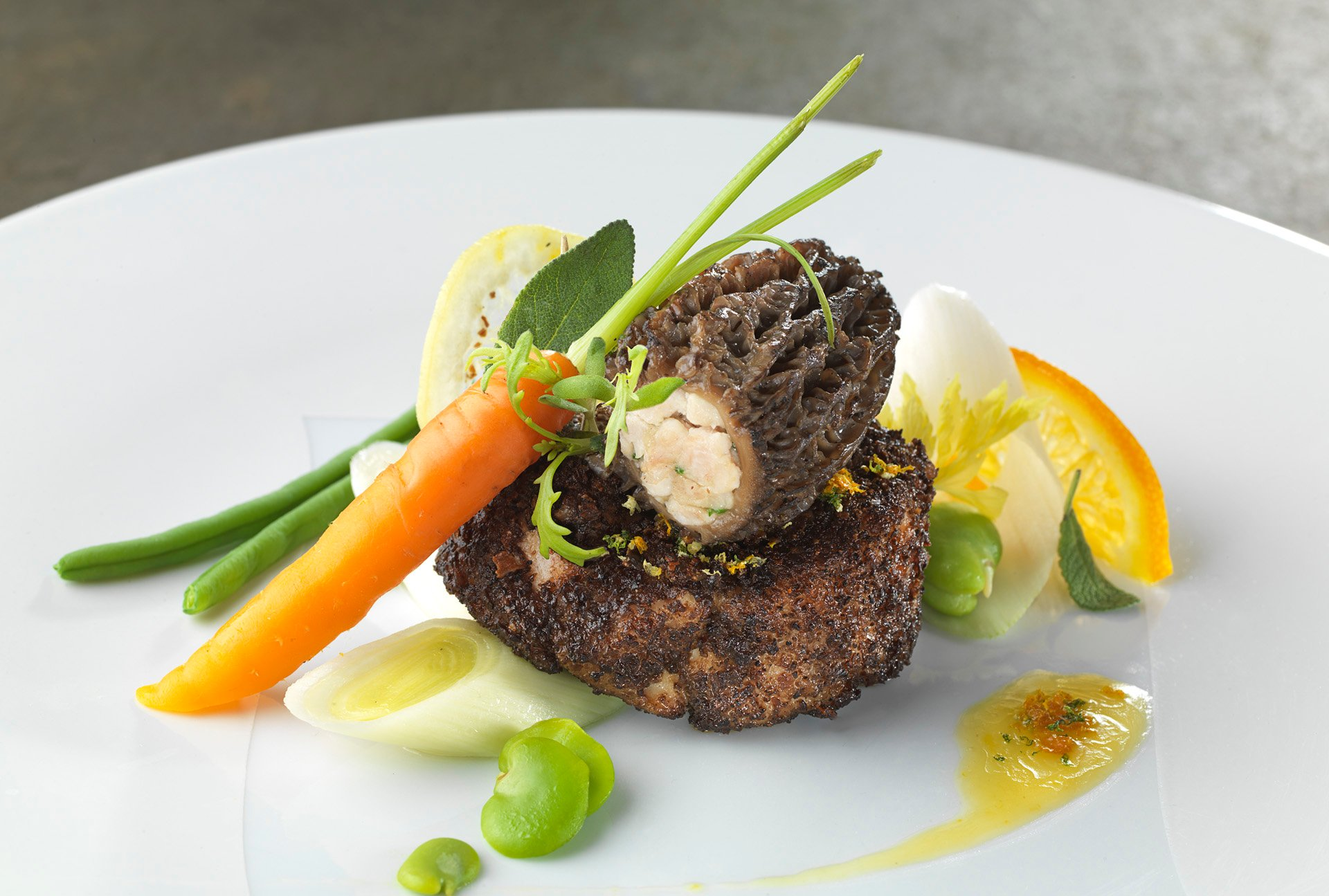 Fantasy of veal sweetbreads coated in morel mushrooms, fresh vegetables with citrus butter